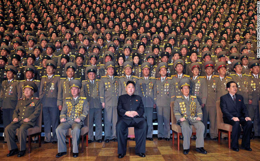 In a still from the video, Kim Jong-un relaxes against a backdrop of uniformed entourage.